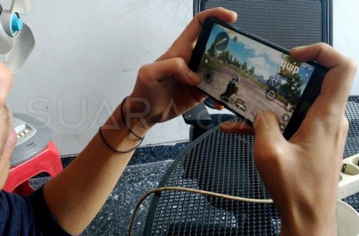 Warga main PUBG Mobile melalui smartphone di Jakarta, Kamis (20/6). [Suara.com/Oke Atmaja]